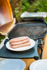 Raw sausages on a plate next to the barbecue