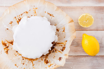 Lemon cake with white icing and fresh lemons
