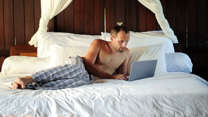 Young man with laptop computer lying on bed