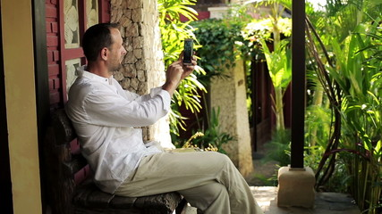 Man taking photo with cellphone, sit on bench