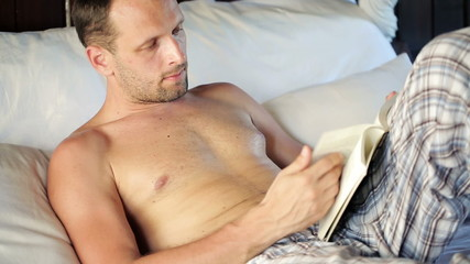 Young man reading book on comfortable bed