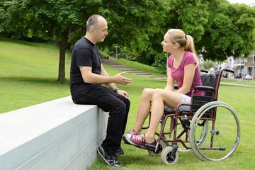 Frau im Rollstuhl mit Freund im Park