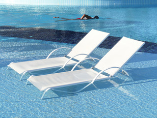 Two chaise longue at the poolside