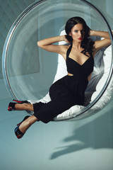 Sexual girl with dark hairs, sitting on a round chair