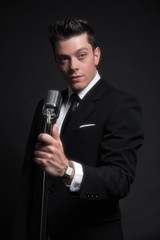 Retro fifties male singer with vintage microphone. Wearing black