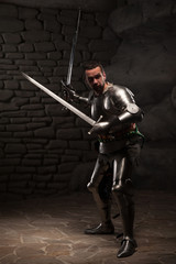 Medieval Knight posing with two swords on in a dark stone wall b