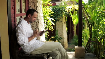 Man with tablet computer sitting on bench