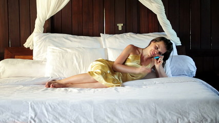 Sexy woman lying on bed and talking on cellphone