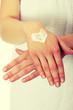 Woman with heart shape cream on hand.