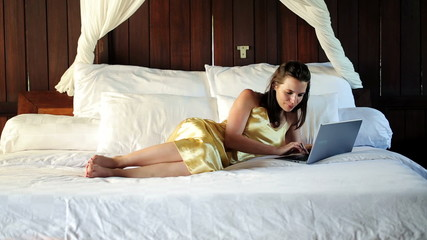 Sexy woman with laptop lying on big comfortable bed