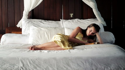 Young woman reading book on big comfortable bed