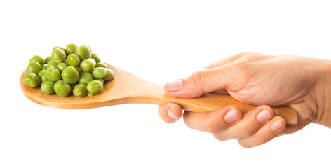 Female hand holding green peas on wooden spoon
