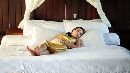 Young woman sleeping on big comfortable bed