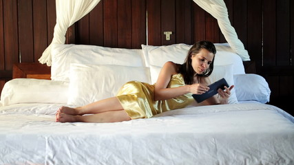 Elegant woman with tablet computer lying on big comfortable bed