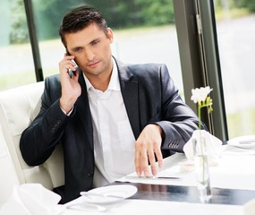 Handsome businessman talking over mobile phone in restaurant