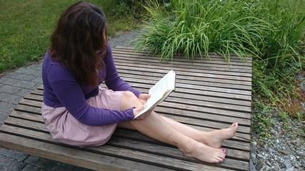 Junge Frau liest sitzend Buch