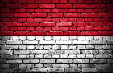Brick wall with painted flag of Monaco