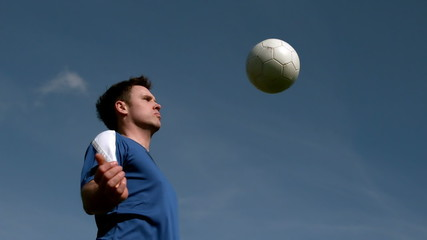 Football player chesting the ball under blue sky