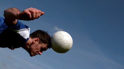 Football player heading the ball under blue sky