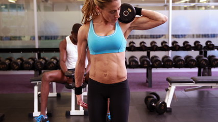 Fit woman lifting dumbbells at crossfit session