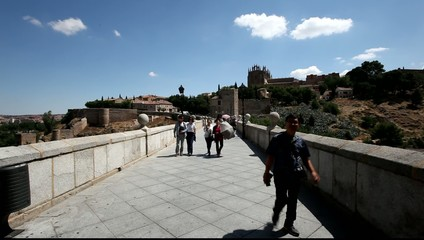 Tourists walking over the San Martin bridge in Toledo, Spain