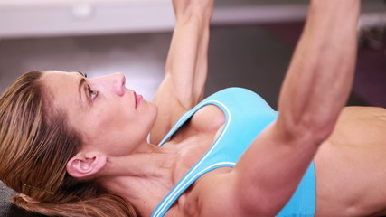 Fit woman lying on bench lifting dumbbells