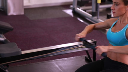 Fit woman using the rowing machine