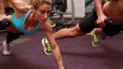 Two fit people lifting dumbbells in plank position