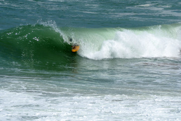 Surfer on  Ocean Wave in the Tube  with yellow surf board