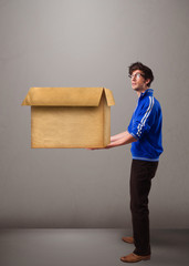 Goog-looking man holding an empty brown cardboard box