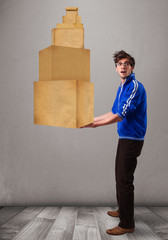Young man holding a set of brown cardboard boxes
