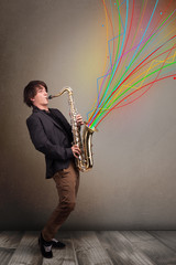 Attractive musician playing on saxophone while colorful abstract