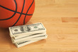 Basketball and one hundred dollar bills on wooden court floor