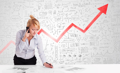 Businesswoman sitting at table with market diagrams
