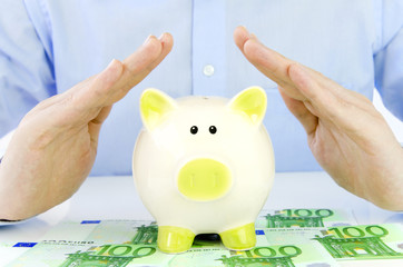 Männliche Hände schützen Sparschwein und Euro-Geldscheine