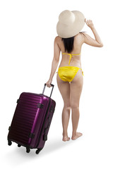 Attractive woman in bikini holding suitcase 1