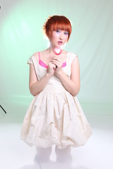 girl with lollipop heart in white dress in studio