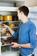 guy looking for something in pan near fridge