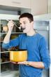 Guy eating soup from pan