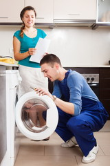 Repairman repairing a washing machine