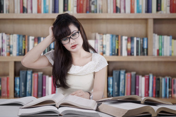 Confused student reading many books 1