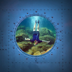 Free diver on the bottom. Submarine window with view to sea.