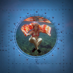 Young woman dancing underwater. Submarine window with view.