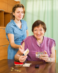 Smiling daughter asking aged mother   money