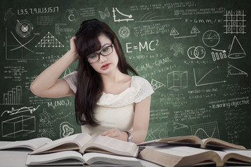 Confused student reading many books