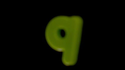 The letter q coming into focus on black background