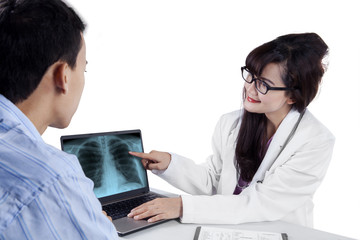 Doctor showing treatment result on laptop