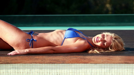 Sexy blonde in blue bikini relaxing lying poolside