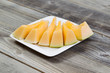 Fresh Melon Slices on White Plate with rustic wood underneath
