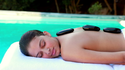 Peaceful brunette getting hot stone massage poolside
